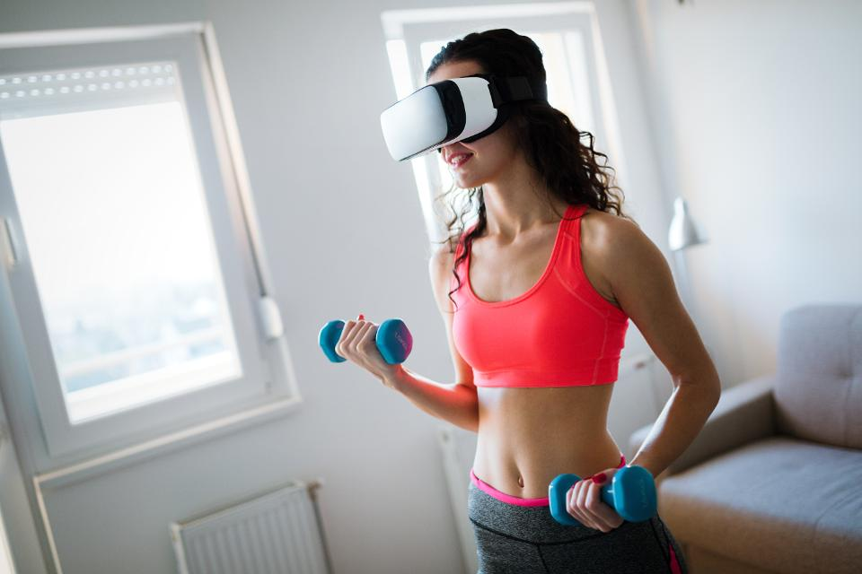 Young woman doing exercises wearing vr goggles